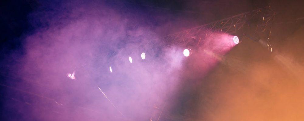 stage spotlight shining through colored smoke